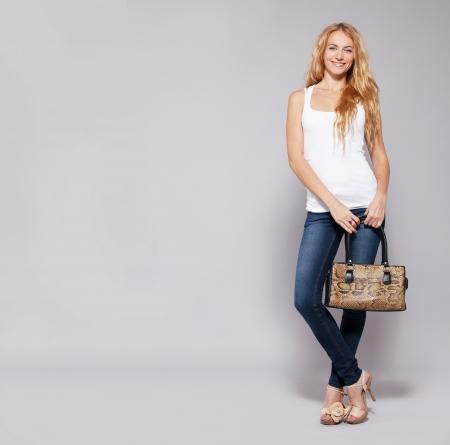Gelukkige vrouw met handtas in de studio