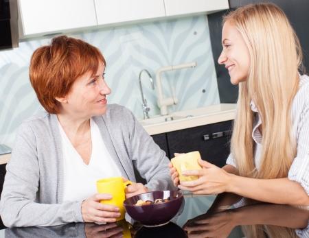 dos personas conversando: Madre y daudhter habla en la cocina. Las mujeres en el hogar Foto de archivo