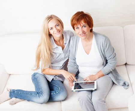 Mother and daughter wiht tablet at sofa. Two women with tablet computer. Family at home on sofa photo