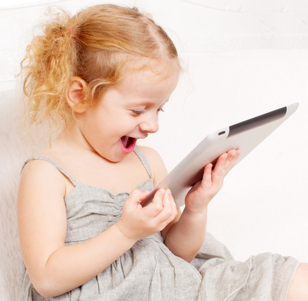 Child with tablet computer. Little child playing at home on sofa photo
