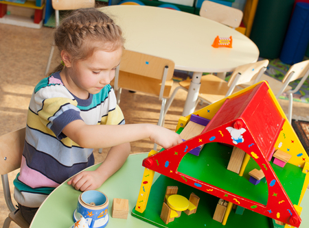 day care center: Child in kindergarten. Kids in nursery school. Girl playing at infant school. Game