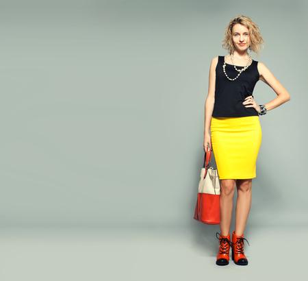 Happy woman with handbag in studio