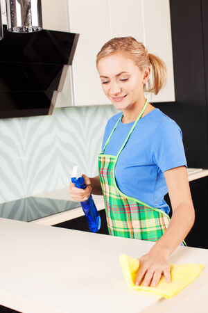 Woman cleaning kitchen. Young woman washing house photo