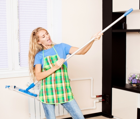 Funny woman with mop. Female cleaning home photo