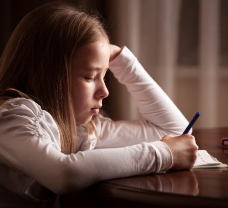 one girl only: Child doing homework. Sad girl writing, reeding Stock Photo