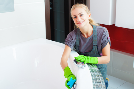 Woman cleaning bath at home. Female washing bath photo