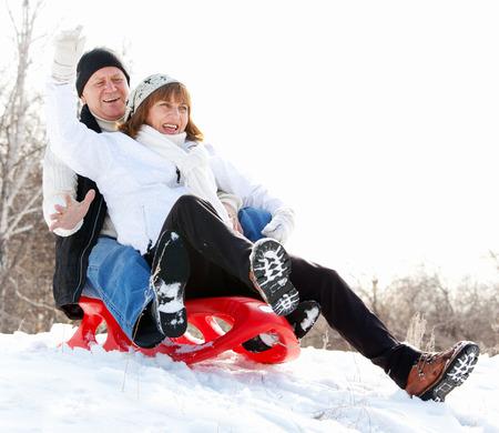 sledding: Mature couple sledding. Seniors couple on sled in winter park Stock Photo