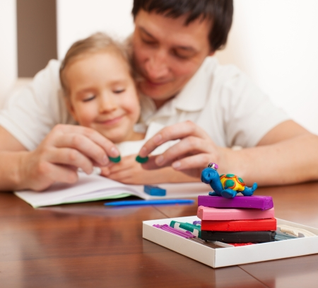 molded: Family molded from clay toys. Father play with child at home
