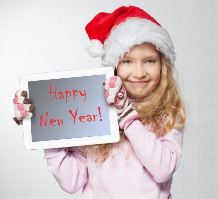 Child in christmas hat with tablet pc. Happy girl showing tablet screen photo