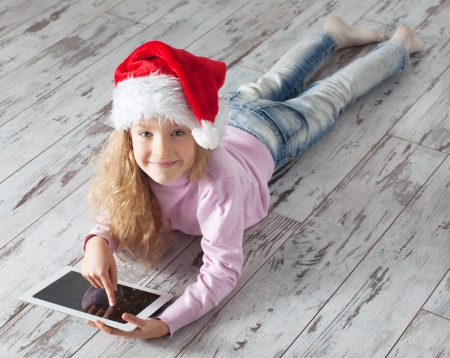 Child in christmas hat with tablet lying on floor. Girl playing computer photo