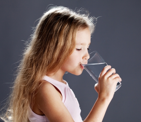 girl drinking water: Child drinking water from glass