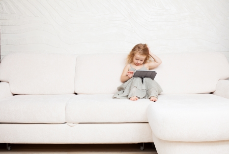 Baby with tablet computer. Little child playing at home on sofa photo