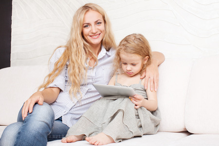 Family wiht tablet at sofa. Woman and baby with tablet computer. Mother and daughter at home on sofa photo