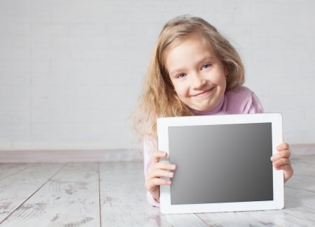 Child with tablet lying on floor. Girl playing laptop computer photo