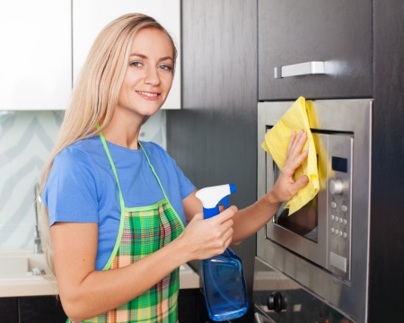 Woman cleaning microwave at kitchen. Female doing housework photo