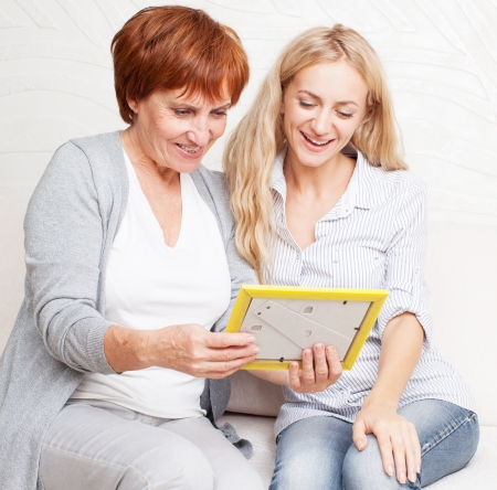 Mother with daughter looking at photo frame. Happy smiling women talking at home