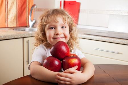 eating fruits: Ni�o que come las frutas. Muchacha en la cocina con la manzana Foto de archivo