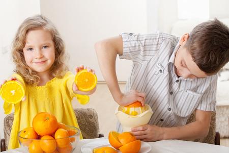 mandarin oranges: Children with oranges. Boy and girl squeezed orange juice.