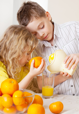 2 persons only: Children with oranges. Kids squeezed orange juice.