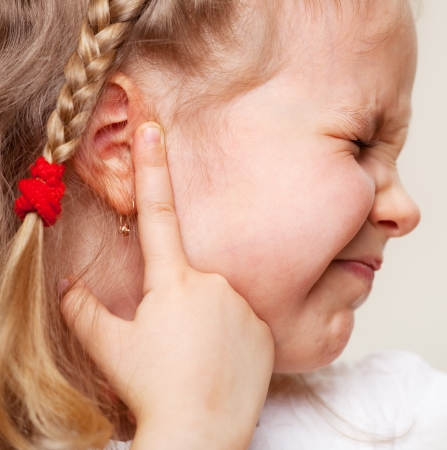dolor de oido: El niño tiene un oído dolorido. Niña que sufre de otitis