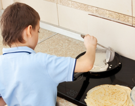 cook griddle: Child bakes pancakes in the kitchen. Boy cooking breakfast Stock Photo