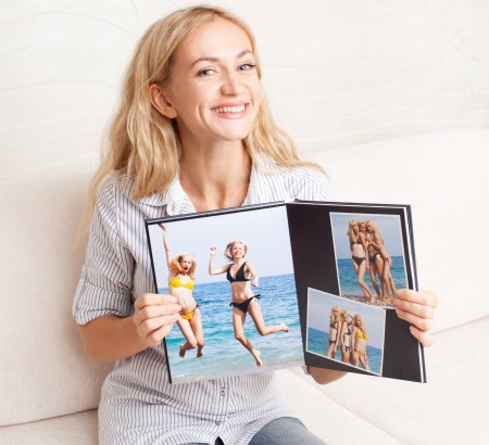 photo album: Young woman showing photo book. Female with photography album