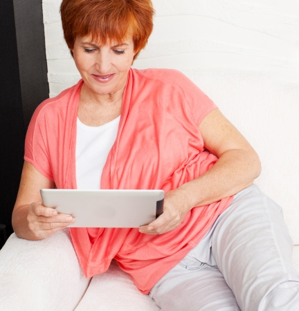 Mature woman with tablet pc. Female with computer at home photo