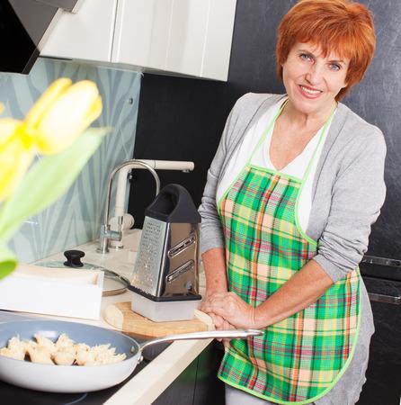 Female cooking at kitchen. Woman preparing pasta photo