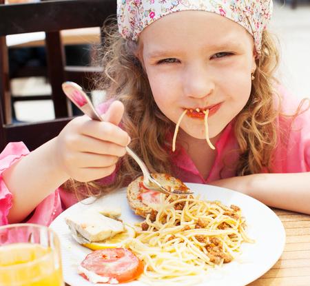 Child eating pasta at cafe photo