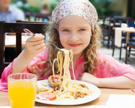 Child eating pasta at cafe photo