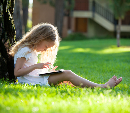 Child with tablet pc outdoors. Little girl on grass with computer photo