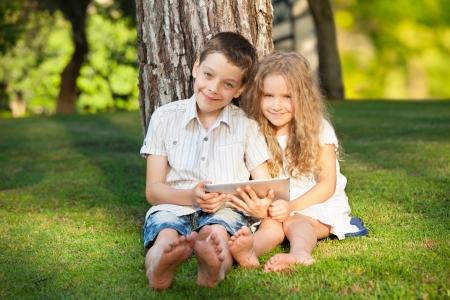 hermanos jugando: Los niños con PC de la tablilla al aire libre. Los niños y niñas en la hierba con la computadora Foto de archivo