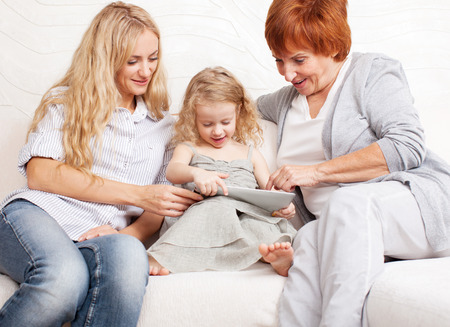 Family wiht tablet computer at sofa. Mother, grandmother and little girl at home on sofa. Generation photo
