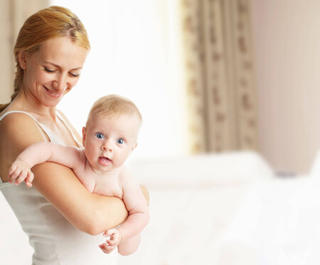 Mother with baby at home. Happy family with newborn indoors photo