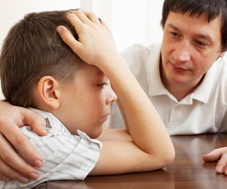 decepción: Padre consuela a un niño triste. Los problemas en la familia