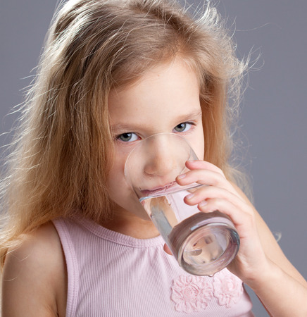 Child drinking water from glass photo