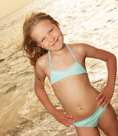 child swimsuit: Vacations  Girl on the beach  Sunset   Stock Photo