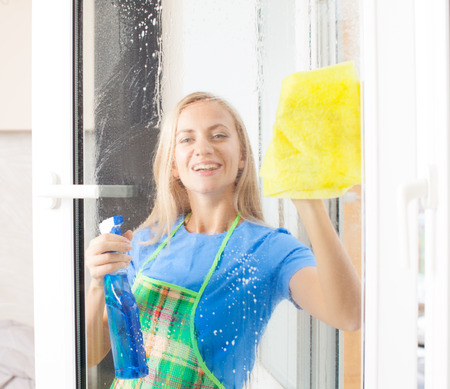 Housewife cleaning window at home photo