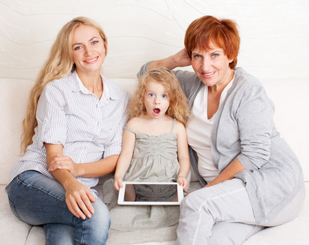 Mother, grandmother and little girl at home on sofa photo