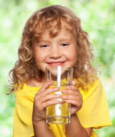 acqua bicchiere: Bambino con un bicchiere di acqua all'aperto