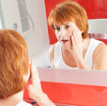 Mature woman gets cream on face in bathroom photo