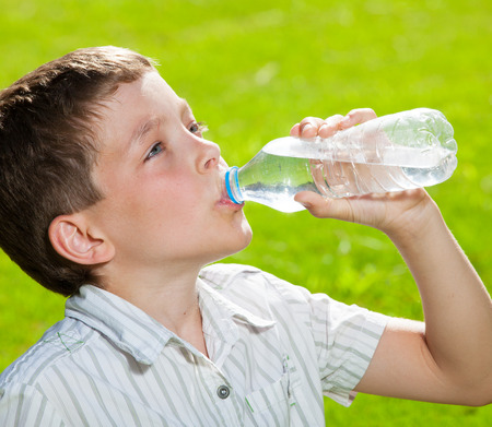 boys only: Child drinking water. Boy outdoors