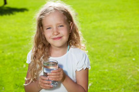 Child drinking water. Girl outdoors photo