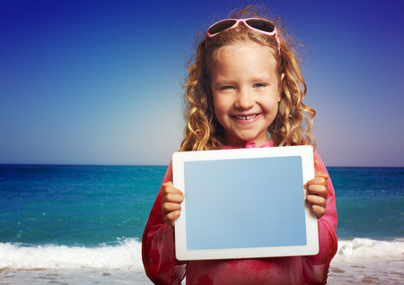 Child on the beach with tablet computer. Little happy girl showing screen digital pc photo