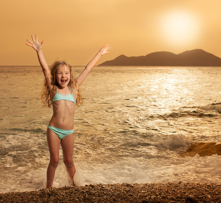 Happy girl on beach at sunset photo