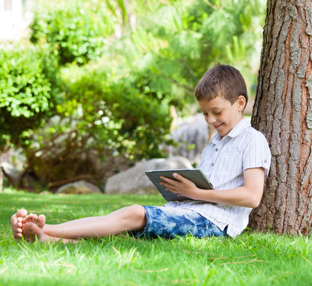 Child with tablet pc outdoors. Boy on grass with computer photo