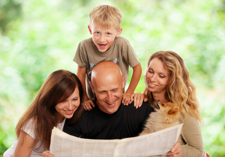 Family reads the newspaper outdoors photo