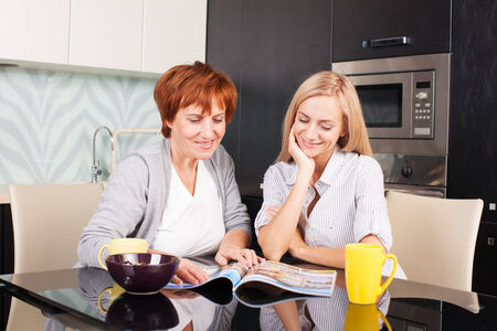 Mother and daughter read magazine at home. Happy women on the kitchen photo