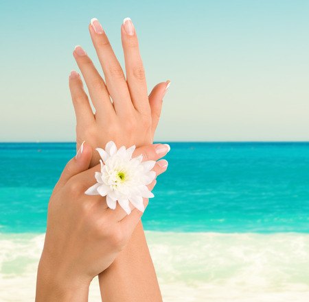 manicure woman: Beautiful female hands on the beach