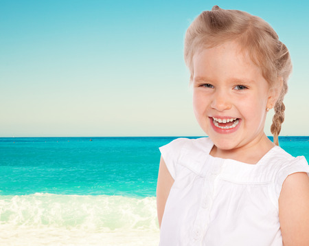 toothe: Little girl on the beach. Happy child Stock Photo